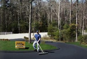Steve Cametti using a squeegee on a freshly coated circular driveway that now looks brand new