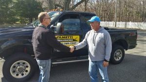 Steve Cametti shaking hands with a homeowner to provide driveway sealcoating services with his truck in the background