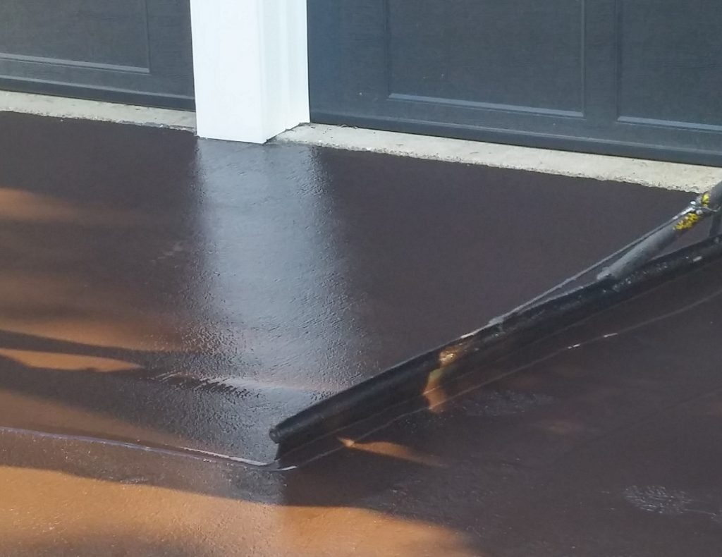 Driveway edges are coated using a small brush to ensure a clean edge