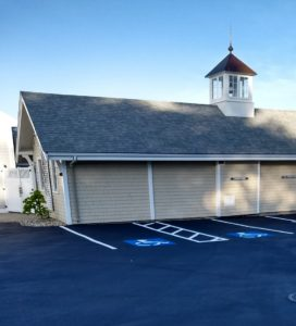 New sealcoat with parking and handicap marks in front of Yacht Club building