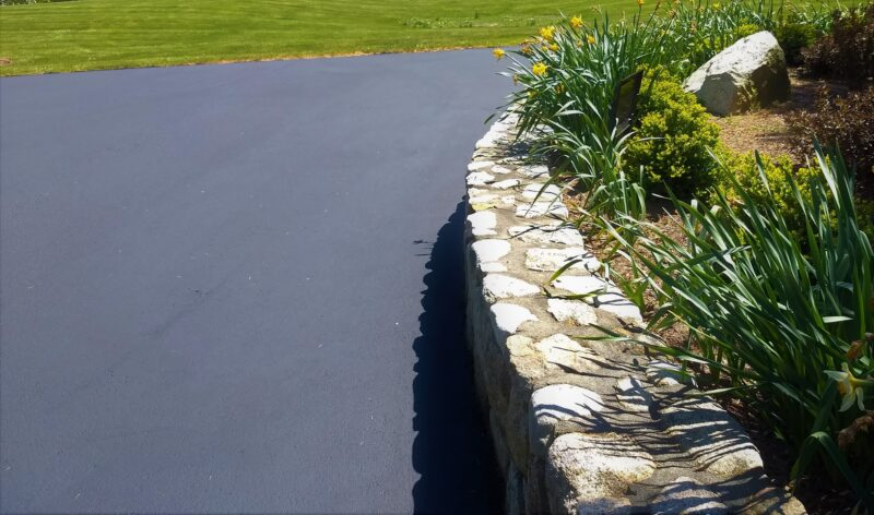 A curved stone wall and garden has an ultra neat appearance after new sealcoating.